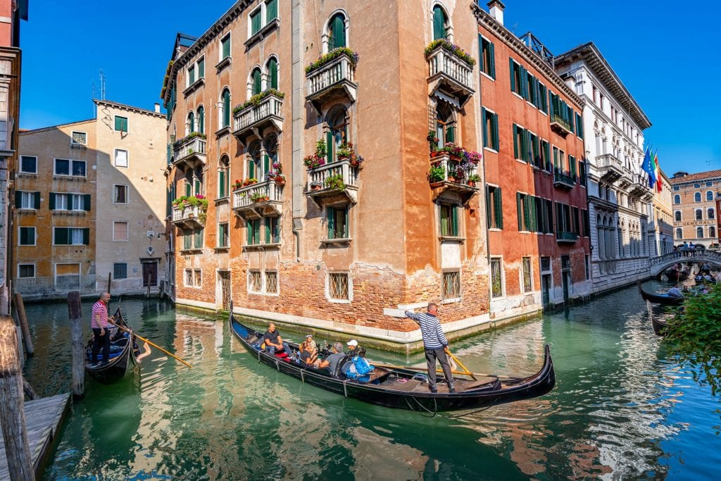 Gondola being steered around a corner between two canals in Venice. Venice's canals were used for many incredible scenes in movies that take place in Italy