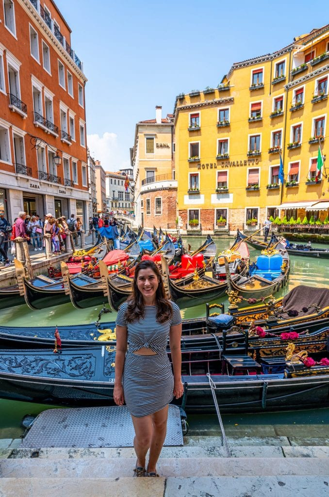 Kate Storm in a striped dress standing in front of a crowd of gondolas near Piazza San Marco with a yellow buidling behind her--if you want to have peaceful gondola ride in Venice, this isn't the best place to get on!