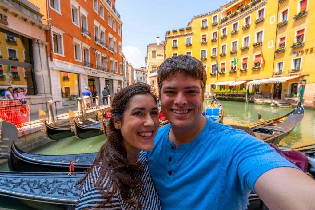 Couple taking a selfie in front of gondolas in Venice.
