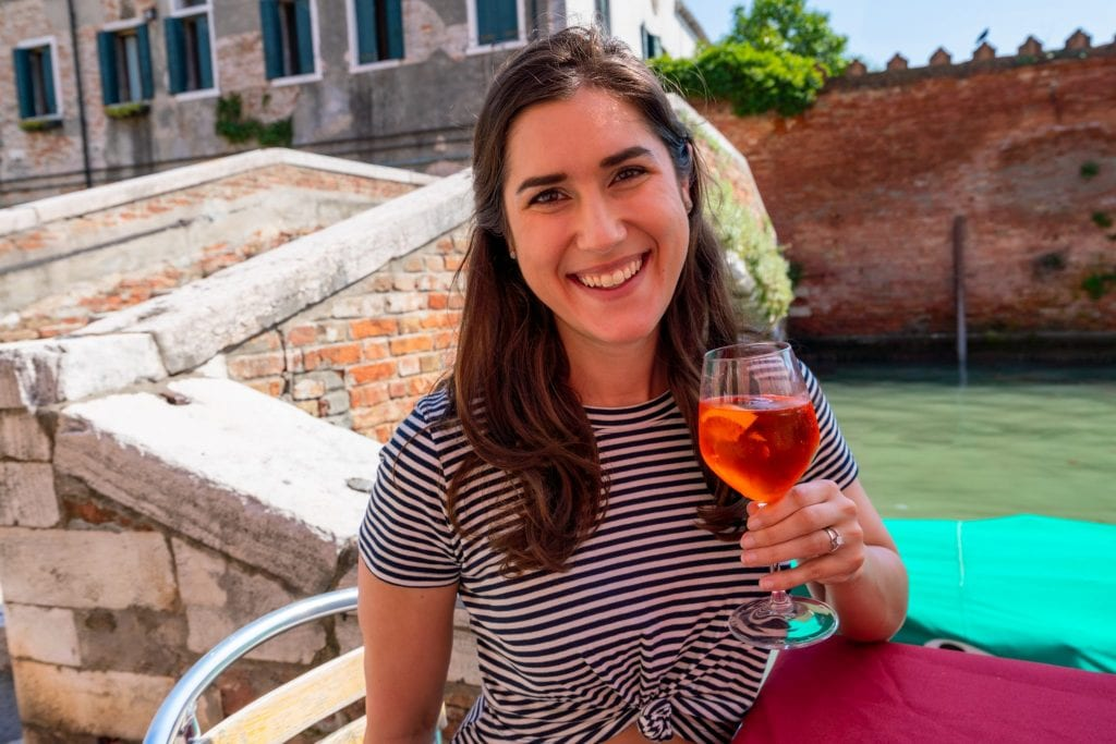 Kate Storm in Venice wearing a striped dress and holding up an Aperol Spritz