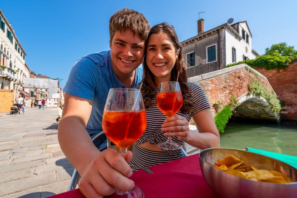 Couple sitting at a table in Cannaregio, Venice, holding aperol spritzes.