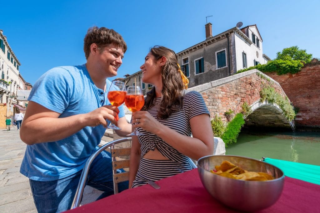 Couple toasting with Aperol Sprtize near a bridge in Cannaregio