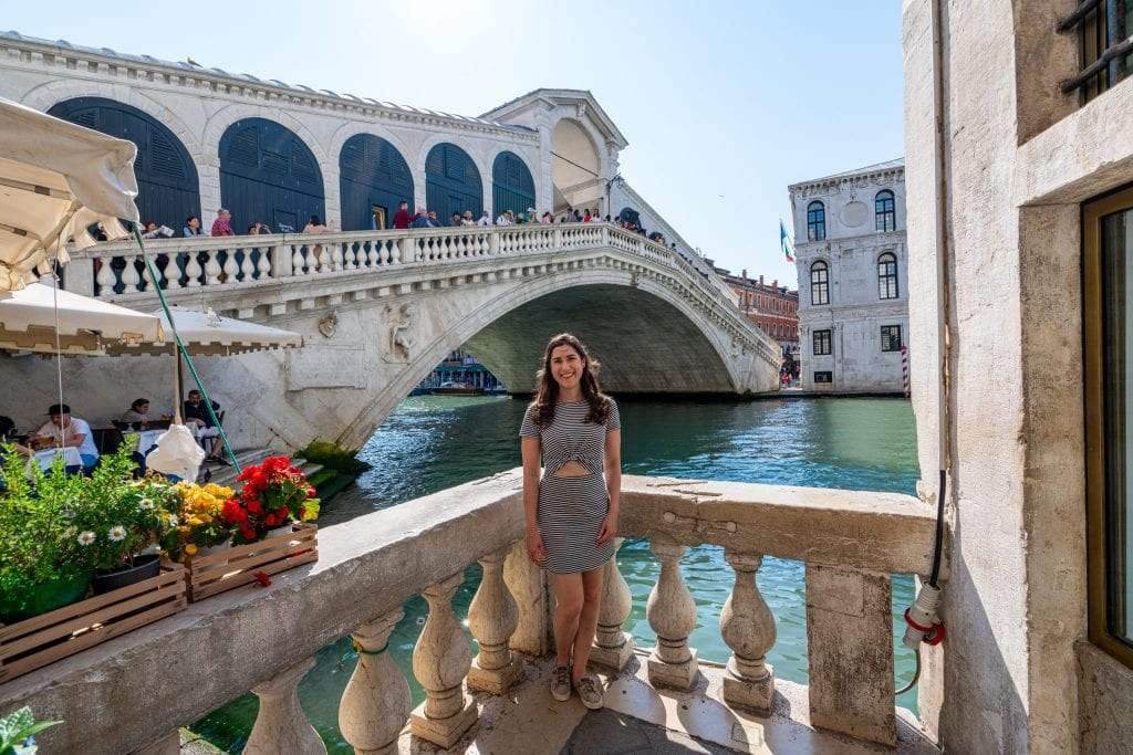 Girl in striped dress standing in front of Rialto Bridge in Venice Italy