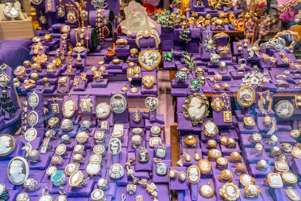 Display of brooches for sale against a purple background in Venice