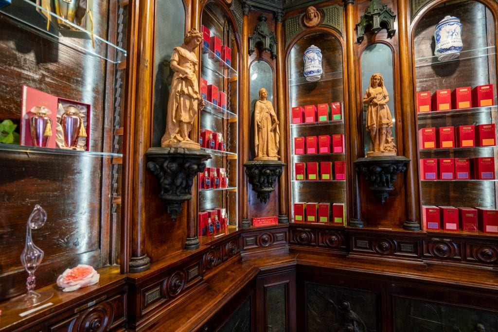 Interior of Merchant of Venice flagship store. There are red bottles of perfume lining the walls, and small stone statues of women decorating the shop.