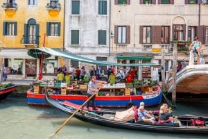 Vegetable barge in Dorsoduro, Venice, with a gondola passing by in front of it