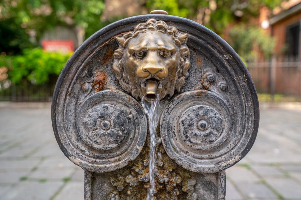 Photo of a small, pretty fountain with a lionhead spout as seen in Venice. One of many travel tips for Italy: you can drink from these fountains!