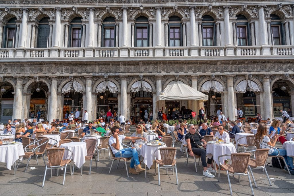 tourists enjoying coffee at an outdoor cafe in famous venice square st marks