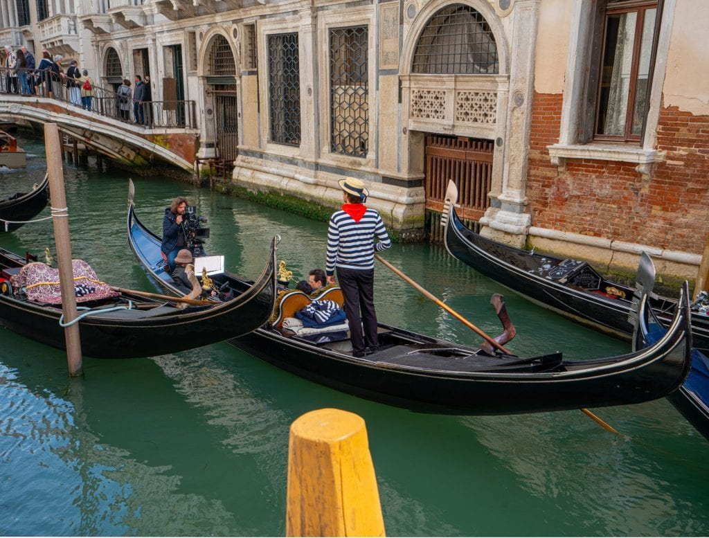 Gondola ride in Venice with a gondlier standing up in the center of the frame. The gondolier has a red bandana on.