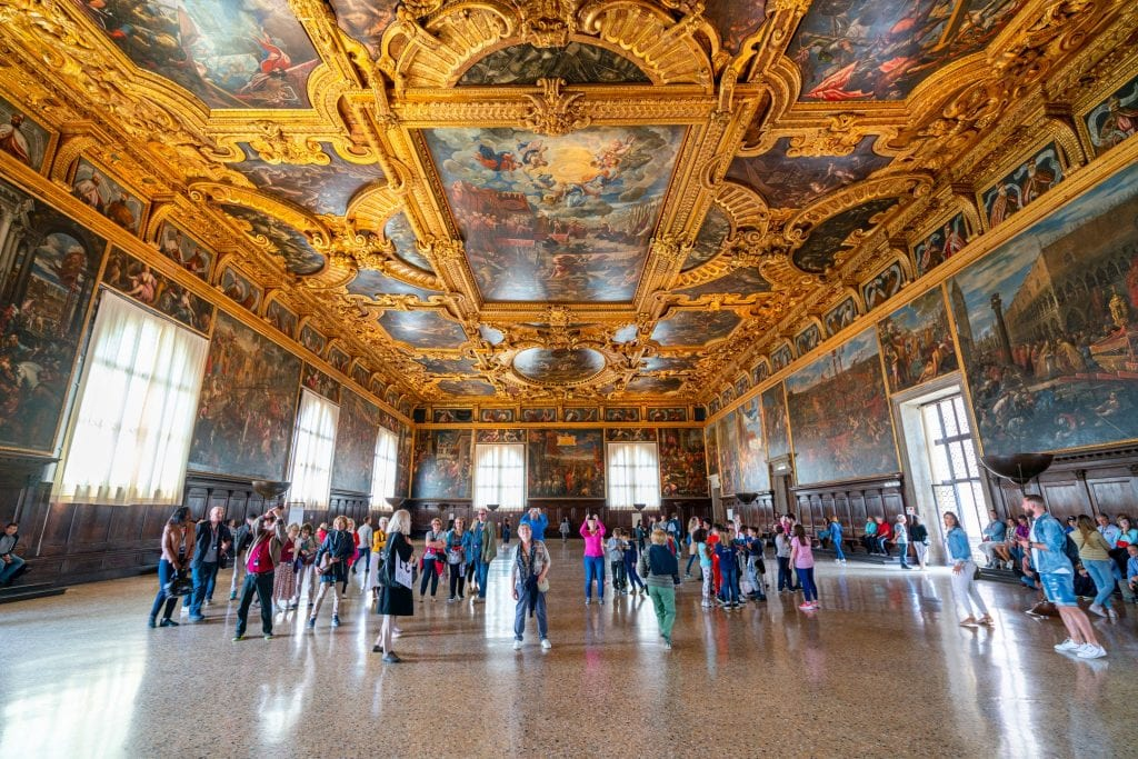 Photo of interior of largest council chamber in the Doge's Palace--definitely worth visiting during one day in Venice! The ceiling is the focus of the shot and is covered in gold, there's a crowd in the distance.