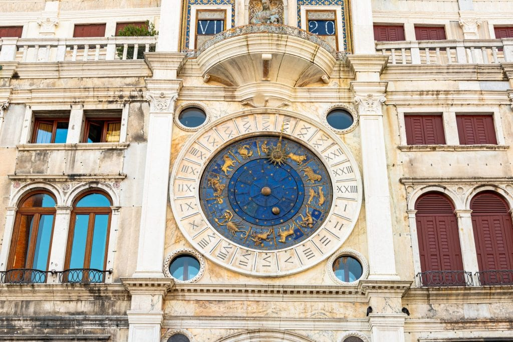 Close up photo of St. Mark's Clocktower with blue face visible. Touring the inside of this beautiful clocktower is a great way to see Venice off the beaten path.