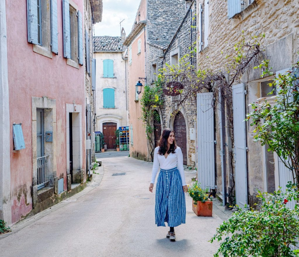 Kate Storm walking down a narrow street in Goult during our France road trip. There's a pink building to her left and she's wearing a long blue skirt.