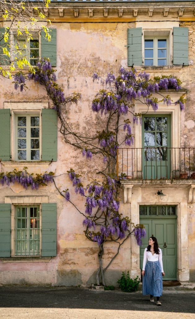 Kate in a long blue skirt standing in front of a building in Goult with green shutters. Wisteria is blooming on the building. Don't miss visiting Goult during your south of France itinerary!