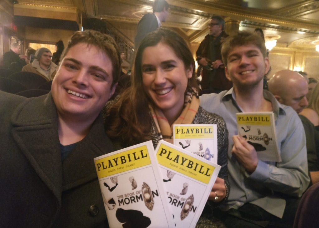Kate and Jeremy with their friend Michael at a Broadway show, holding up playbills for the Book of Mormon