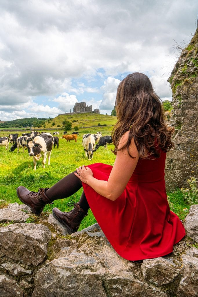 Kate Storm in a red dress at Hore Abbey. She's sitting on a stone wall looking out at a field of cows. Her boots are recommended for your packing list for Ireland!