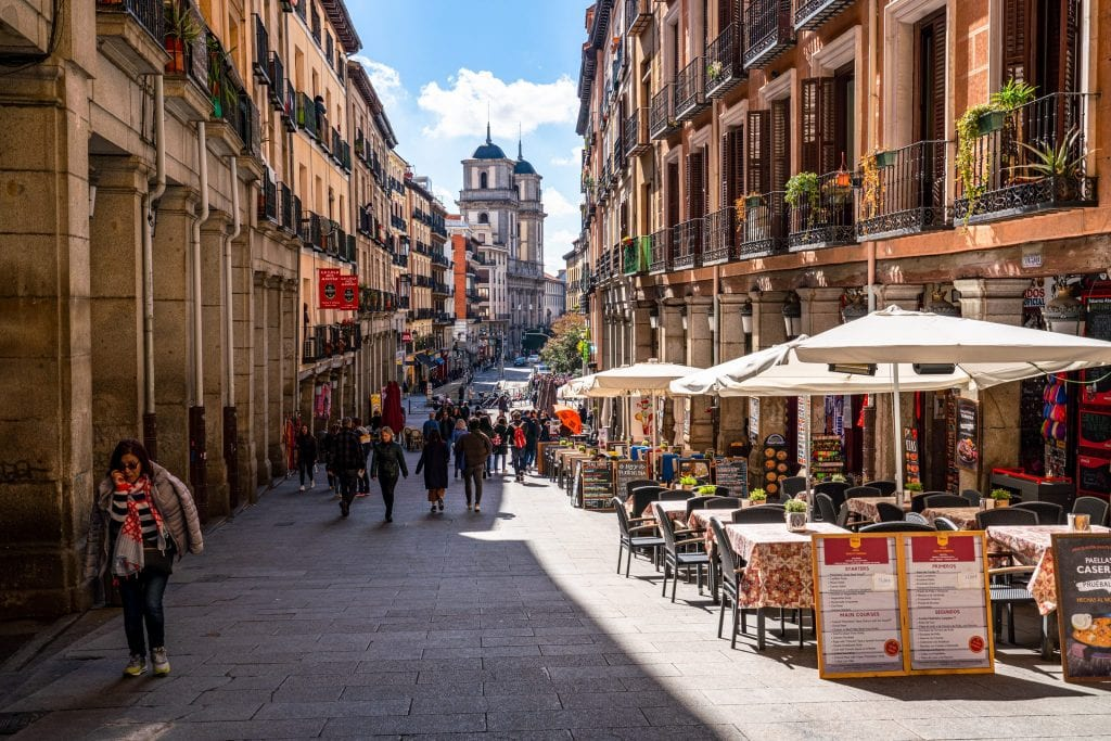 Photo of a quiet street in Madrid Spain, with tables that have umbrellas set over them on the righthand side.