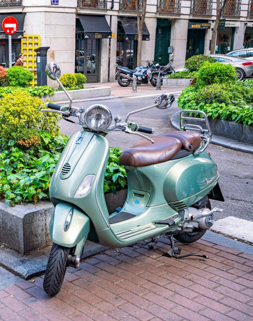 Teal Vespa parked on the corner of a street in Madrid Spain