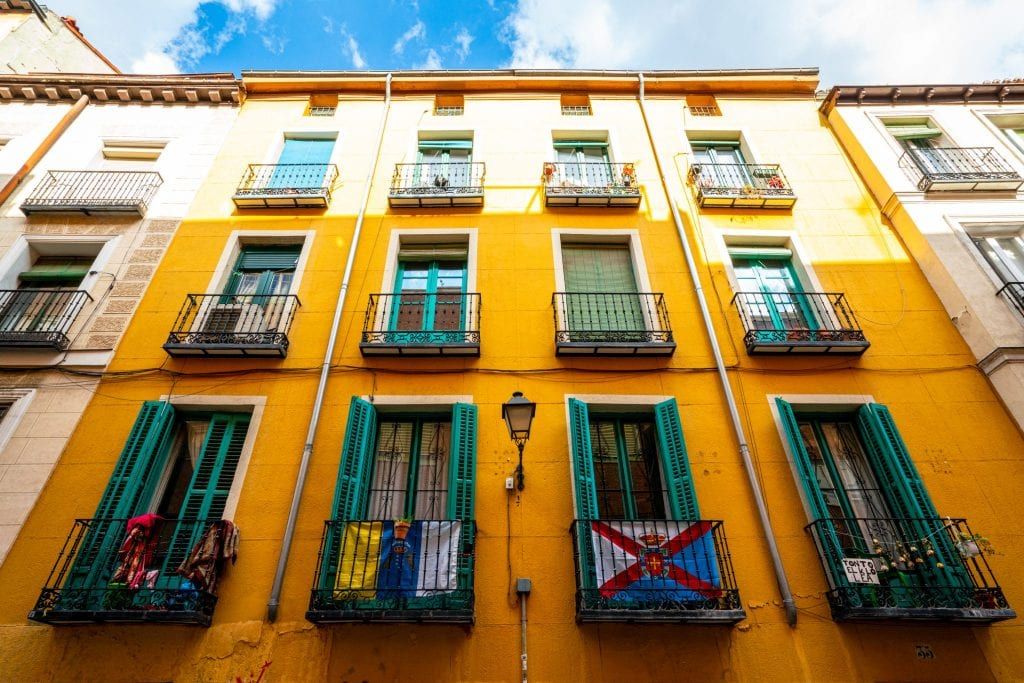 Colorful yellow building with green shutters in La Latina Madrid Spain