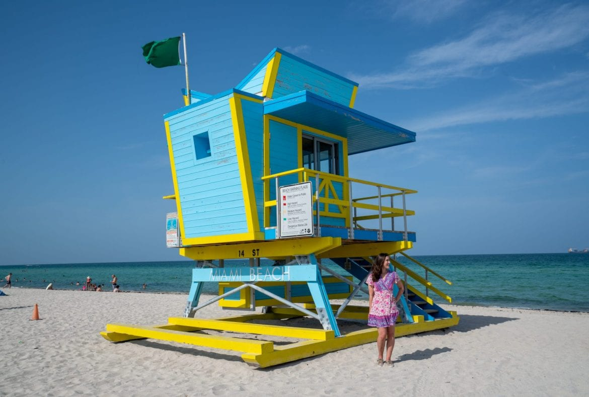 Kate in a pink dress standing in front of a blue art deco lifeguard stand on South Beach in Miami Beach.