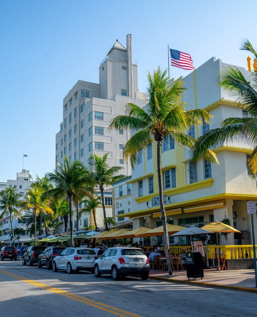 Ocean Drive in Miami Beach, a must see during any trip to Miami! The street is lined with palm trees and there's a yellow and white building in the foreground. An American flag is waving at the top of the photo.