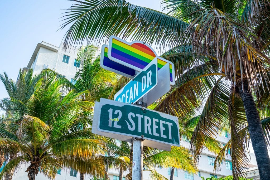 Photo of the sign for cross streets Ocean Drive and 12th Street. There's pride rainbow on top of the sign and palm trees in the background.