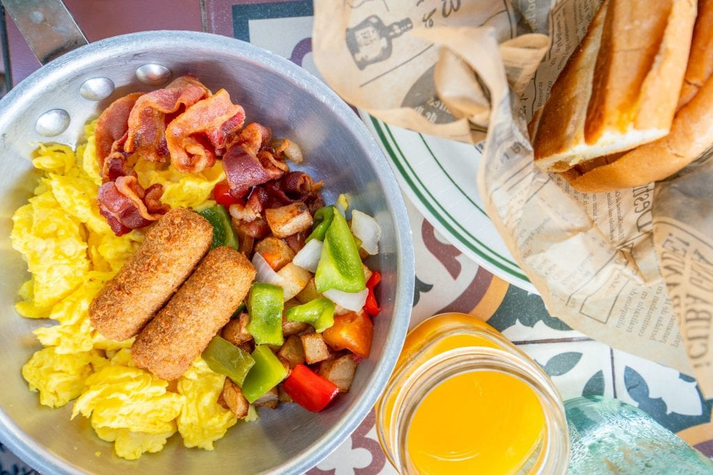 Big Havana Breakfast as served at Havana 1957 in Miami Beach, shot from above. A pan of eggs and croquetas, a basket of bread, a glass of orange juice.