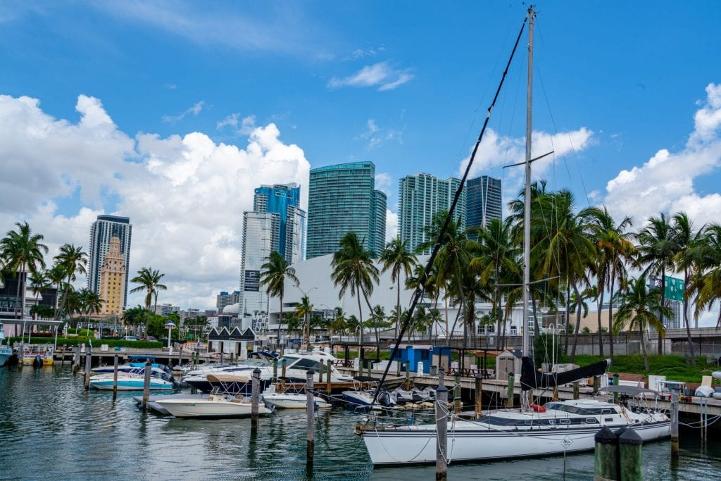 Harbor in Miami. There's a sailboat in the foreground, smaller boats behind it, and skyscrapers visible beyond that.