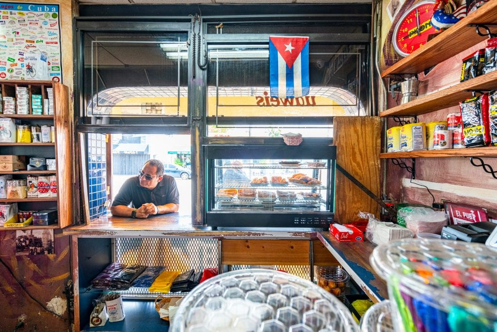 Man standing at the window of El Pub in Little Havana waiting for coffee. There's a case of empanadas to the right and a Cuban flag hanging near the top right of the photo.
