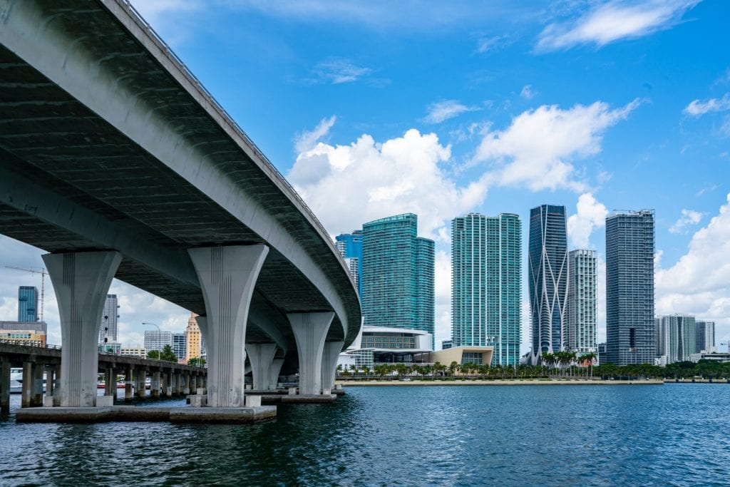 A Miami causeway is on the left of the photo, and a piece of the skyline on the right. The causeway is built over water, visible on the bottom of the photo.