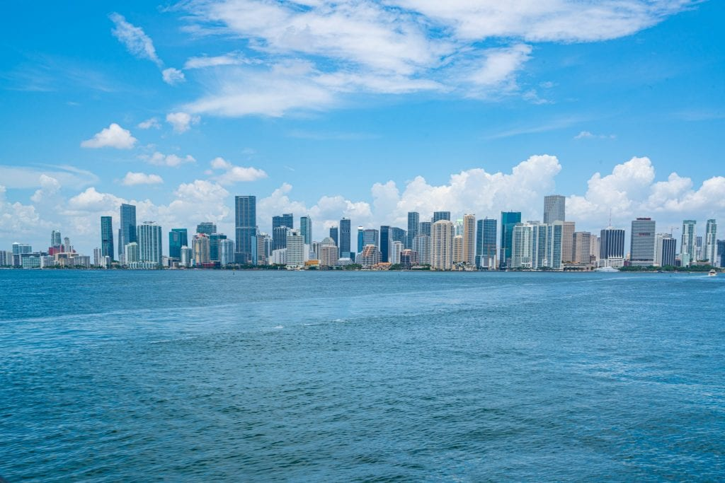 Skyline of downtown Miami as seen from across the Bay. The skyline is in the center of the photo, with water below and blue sky above.