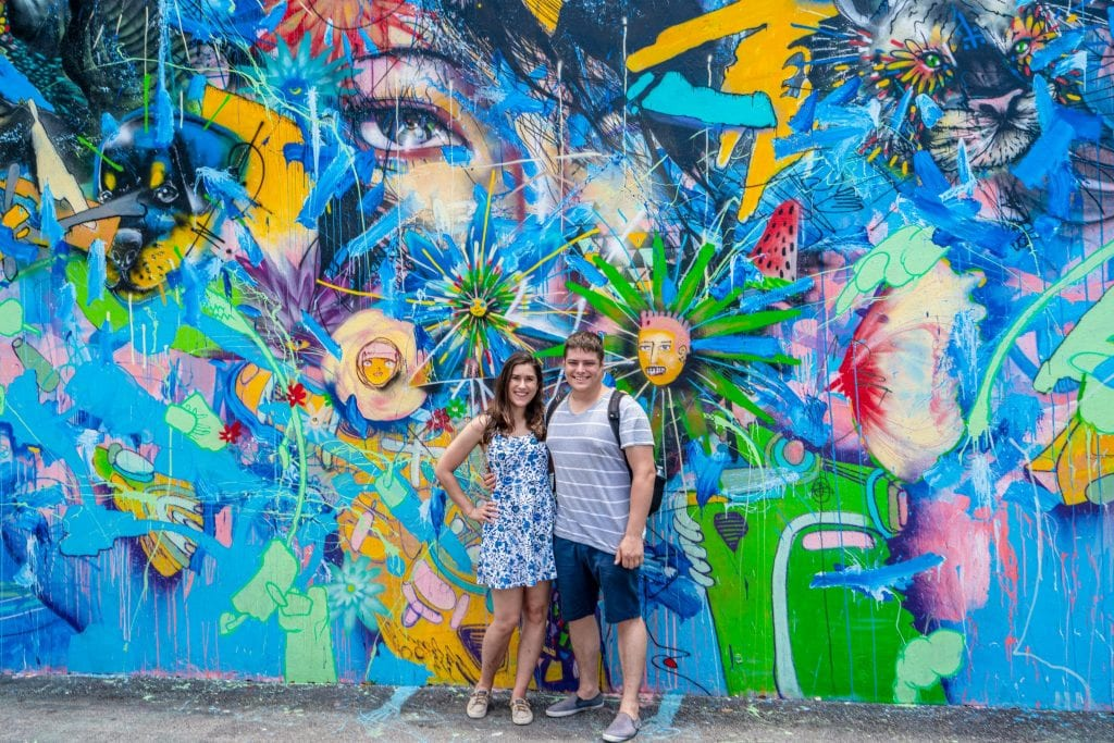 Kate and Jeremy standing in front of a colorful, mostly blue, mural in Wynwood, Miami