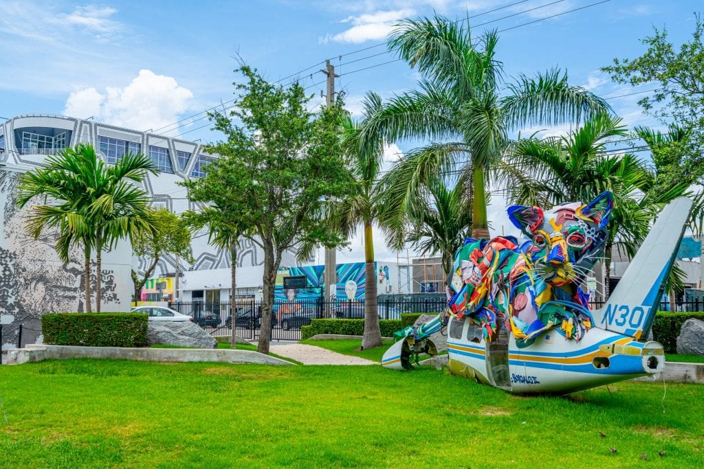 Colorful, painted plane on the ground in Wynwood Walls park. There is grass under the plane and palm trees behind it.