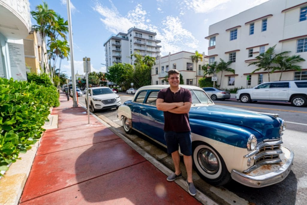 Jeremy standing next to a classic car parked on Collins Ave. There's a sidewalk to the left that is painted maroon.