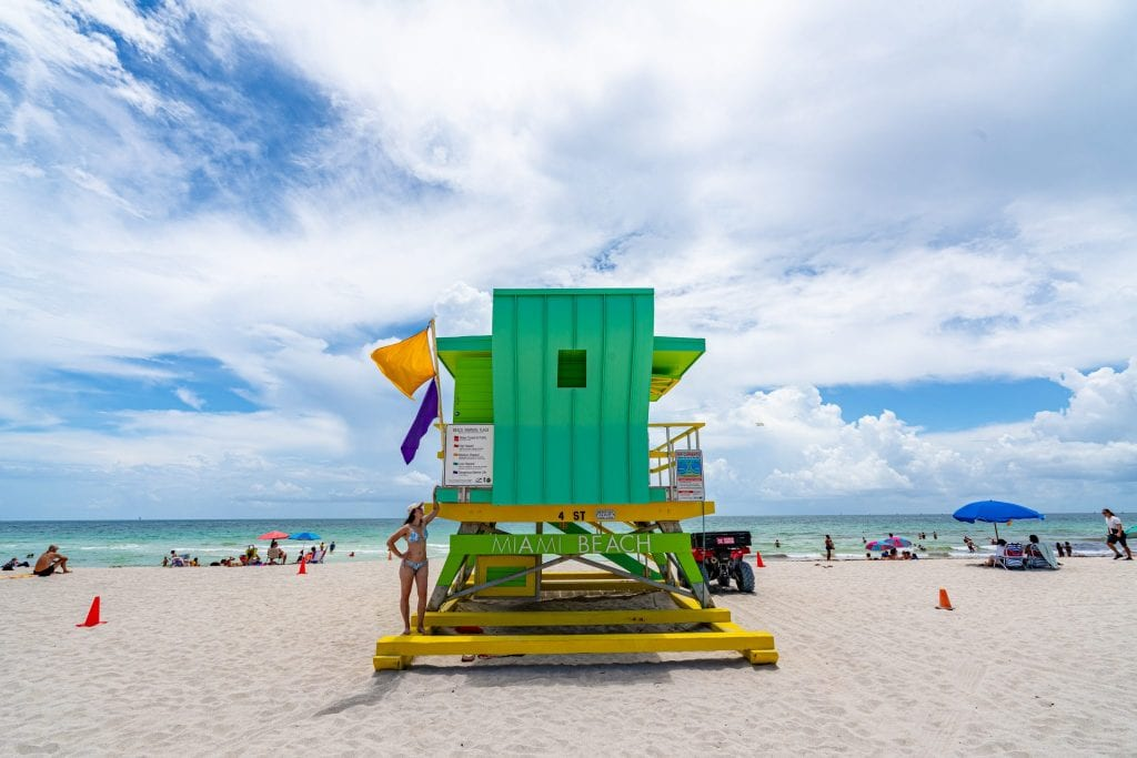 "Kate standing on a green art deco lifeguard stand on South Beach--an essential place to visit during any 3 day Miami itinerary! The lifeguard stand says ""Miami Beach"" and has two flags on it."
