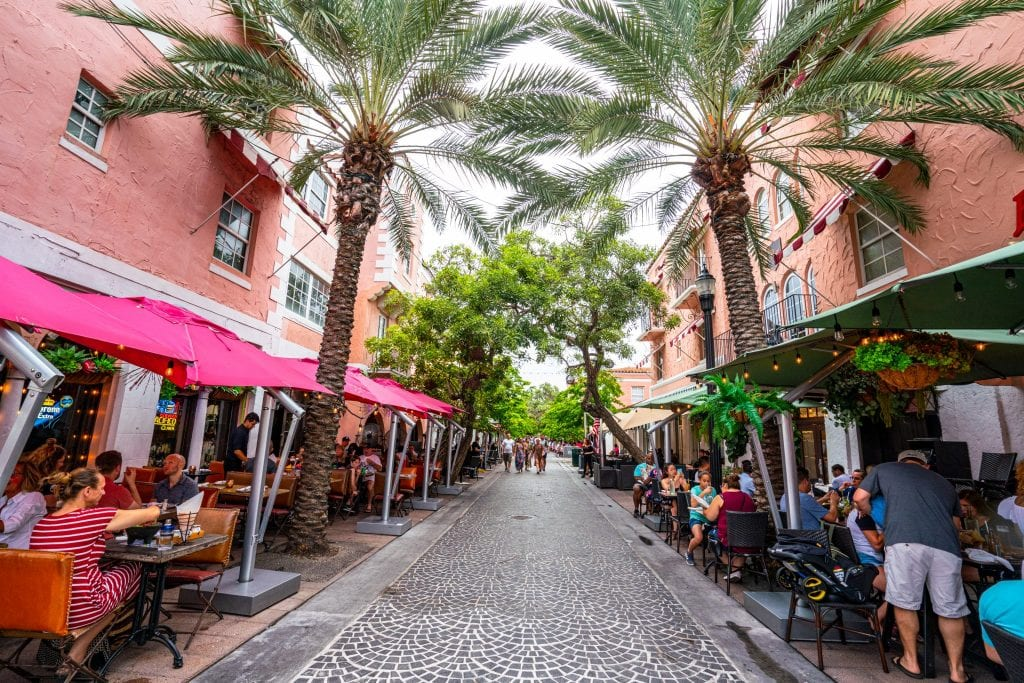 Espanola Way in Miami: the pedestrian street in the center is empty and cobblestone. The street is framed by palm trees and restaurants.
