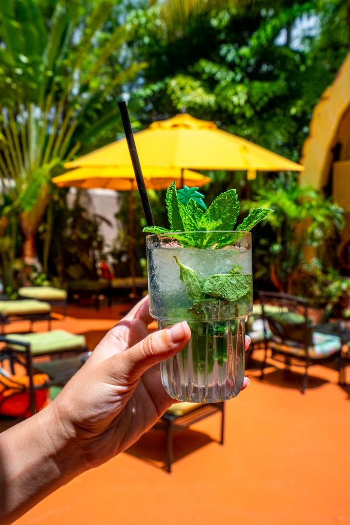 mojito being held in front of a yellow umbrella in miami fl