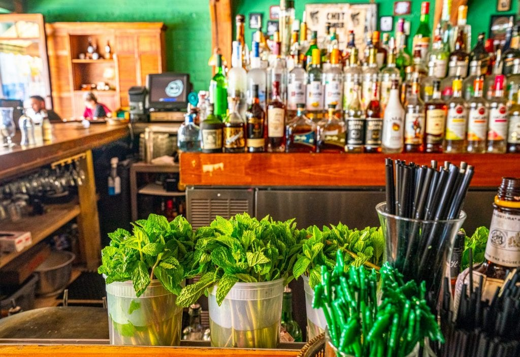 Ball & Chain bar in Little Havana, Miami: fresh mint is in the foreground of the shot, and a full, stocked bar is behind it.
