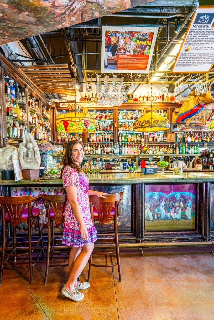 Kate in a pink dress standing in Cubaocho, in front of a historic wooden bar with many glass bottles and hanging lamps. Don't skip this during your long weekend in Miami!