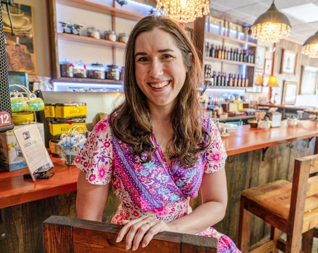 Kate in a pink dress sitting on a bar stool, inside a bar in Little Havana