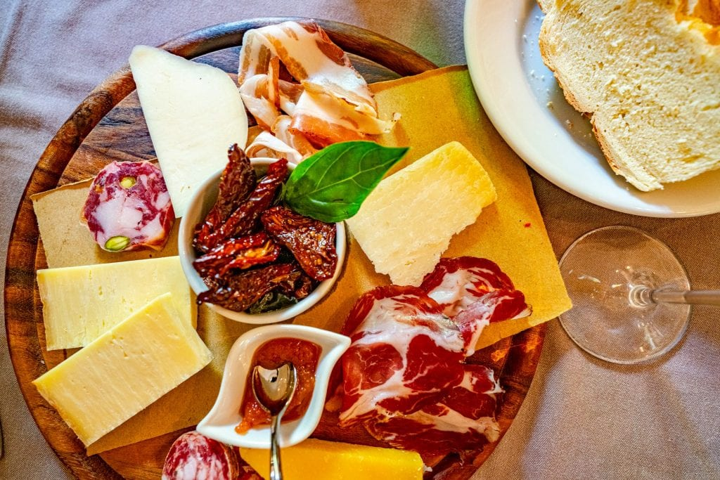 Prosciutto and cheese platter with bread as seen from above--be sure to eat plenty of delicious food like this during your 10 days in Sicily!