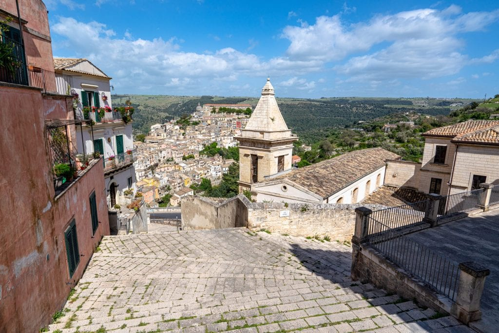 Steep staircase in Ragusa with a church tower on the right and Ragusa Ilba visible in the distance