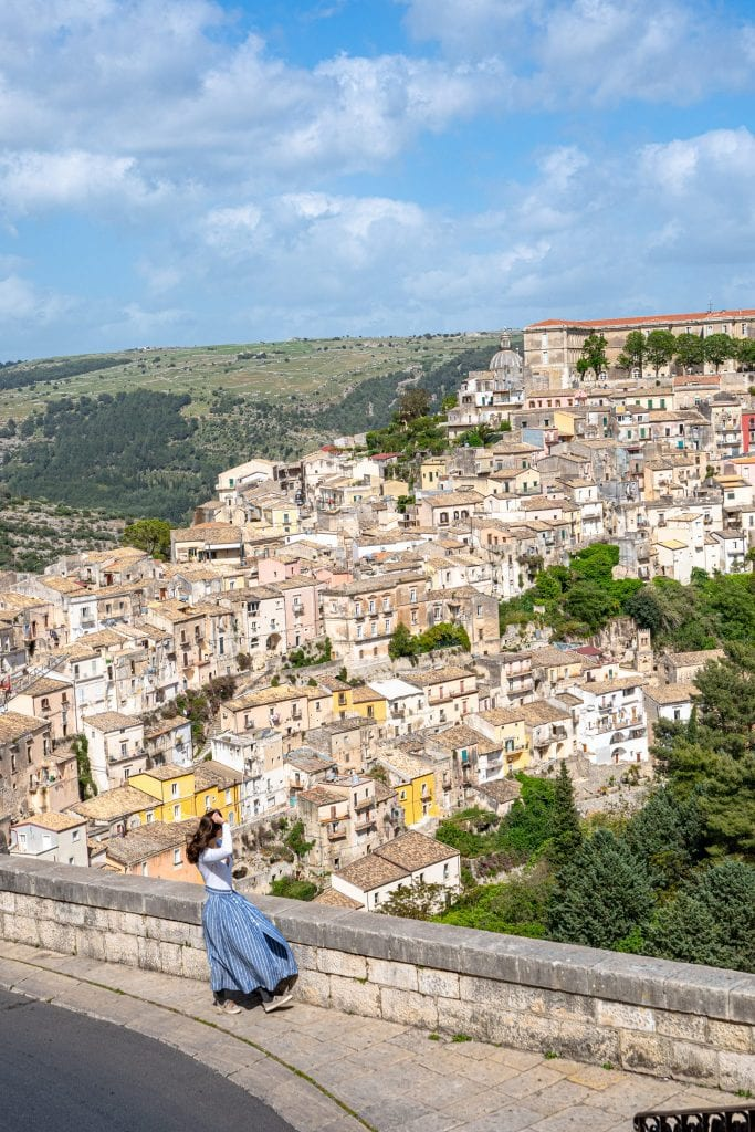 Kate Storm in a blue skirt overlooking Ragusa Ilba from Ragusa Superiore, one of the best views on this 10 days in Sicily itinerary