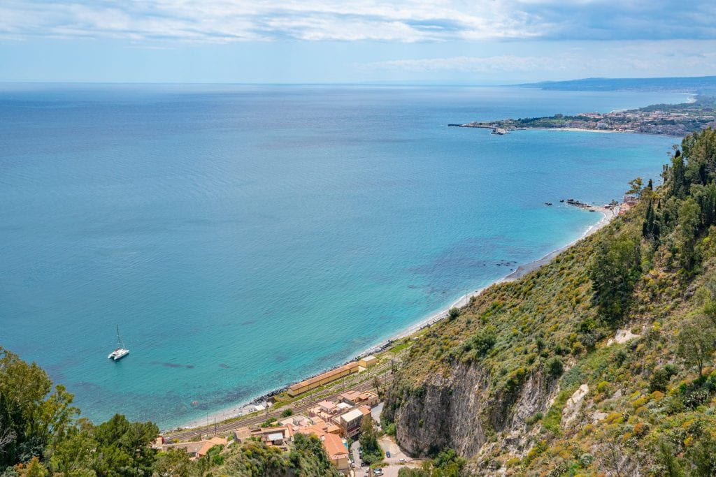 View of Ionian Sea from Taormina Sicily. There's a lone catamaran in the bottom left corner of the photo.