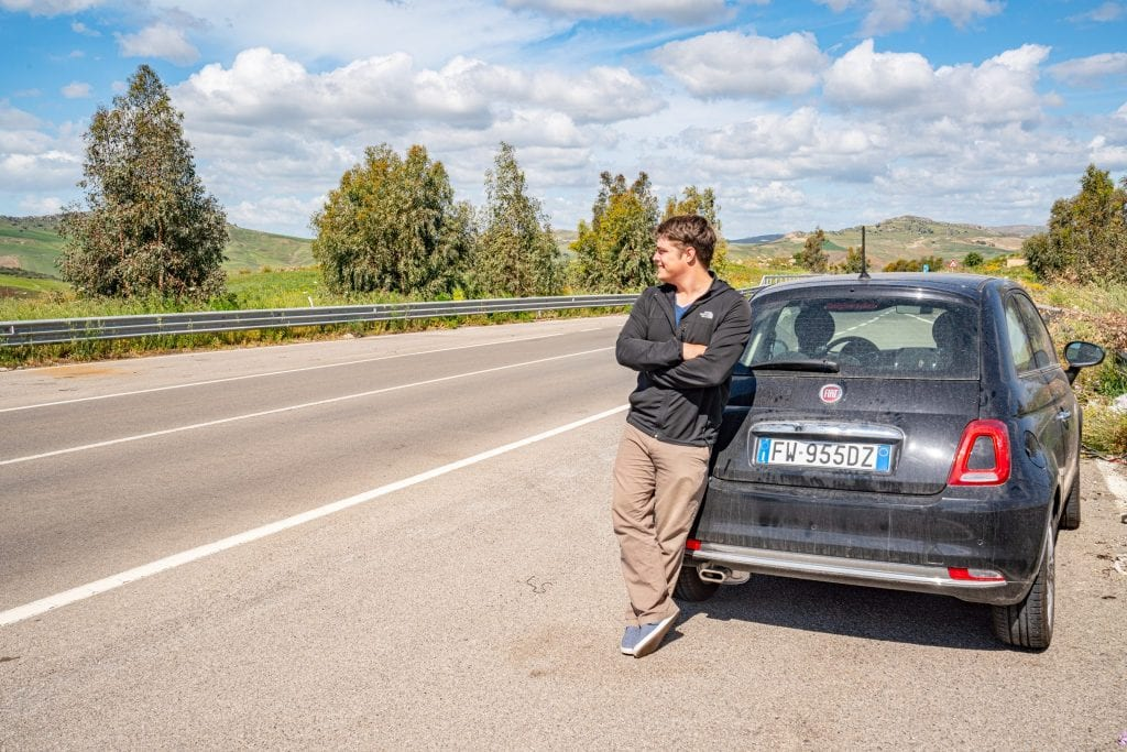 Jeremy Storm leaning against a small black Sicily rental car looking out over an empty road in Sicily