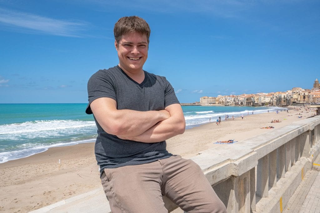 Jeremy Storm sitting on a wall overlooking Cefalu beach, a fabulous stop during a Sicily road trip itinerary