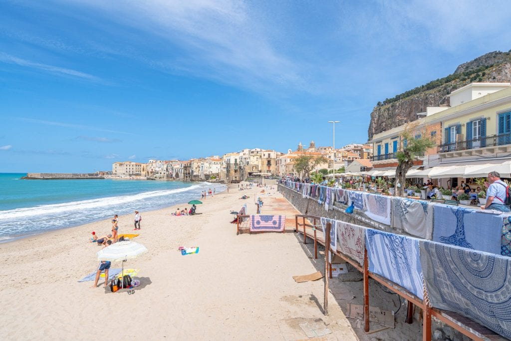 Cefalu Beach in Sicily Italy, with towels for sale on the right and the sea visible on the left, one of the best places to visit in Sicily travel