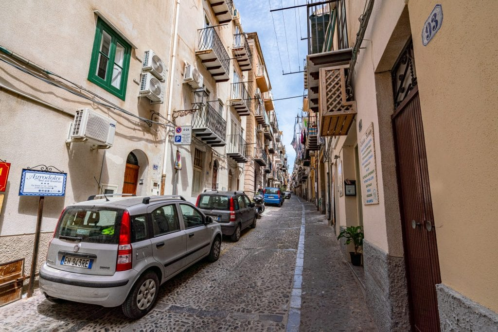 Small street of Cefalu Sicily with cars parked alongside it