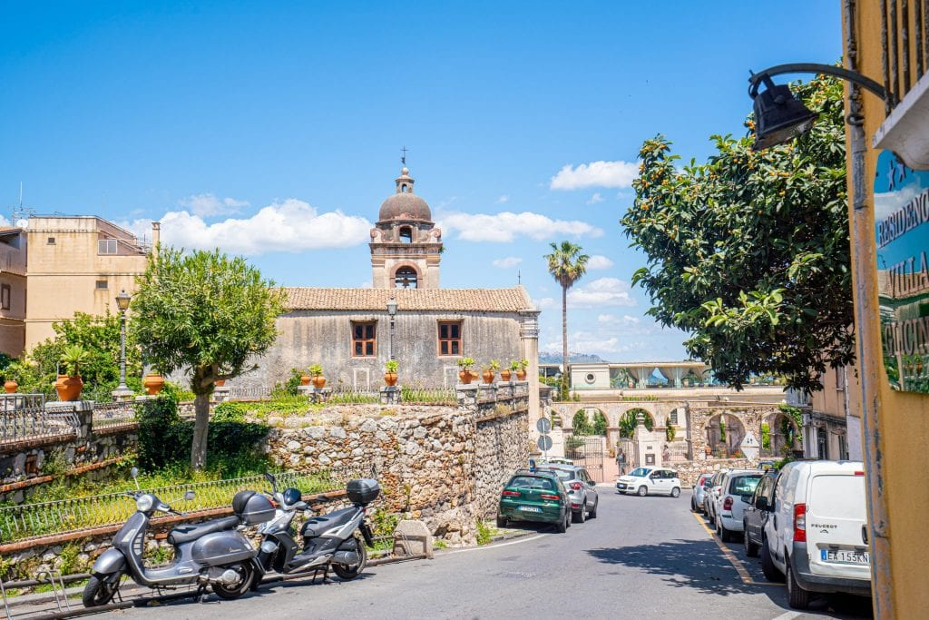 Photo of a street in Taormina Sicily with cars parked on either side. There's a church visible toward the back of the photo.
