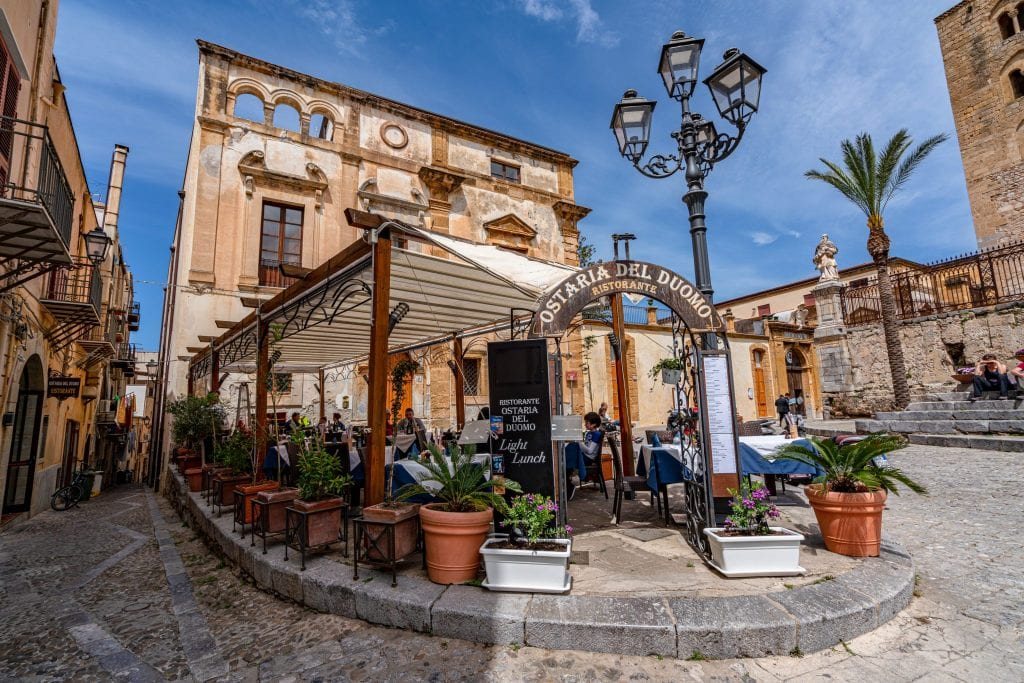 Restaurant with outdoor tables shaded by awnings outdoors in Piazza Duomo in Cefalu, as seen on a Sicily road trip