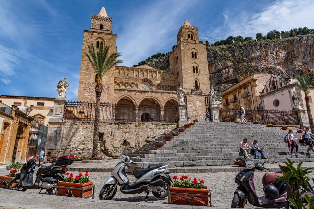 Cefalu Cathedral with a vespa parked in front of it, one of the best things to see on a Sicily road trip itinerary